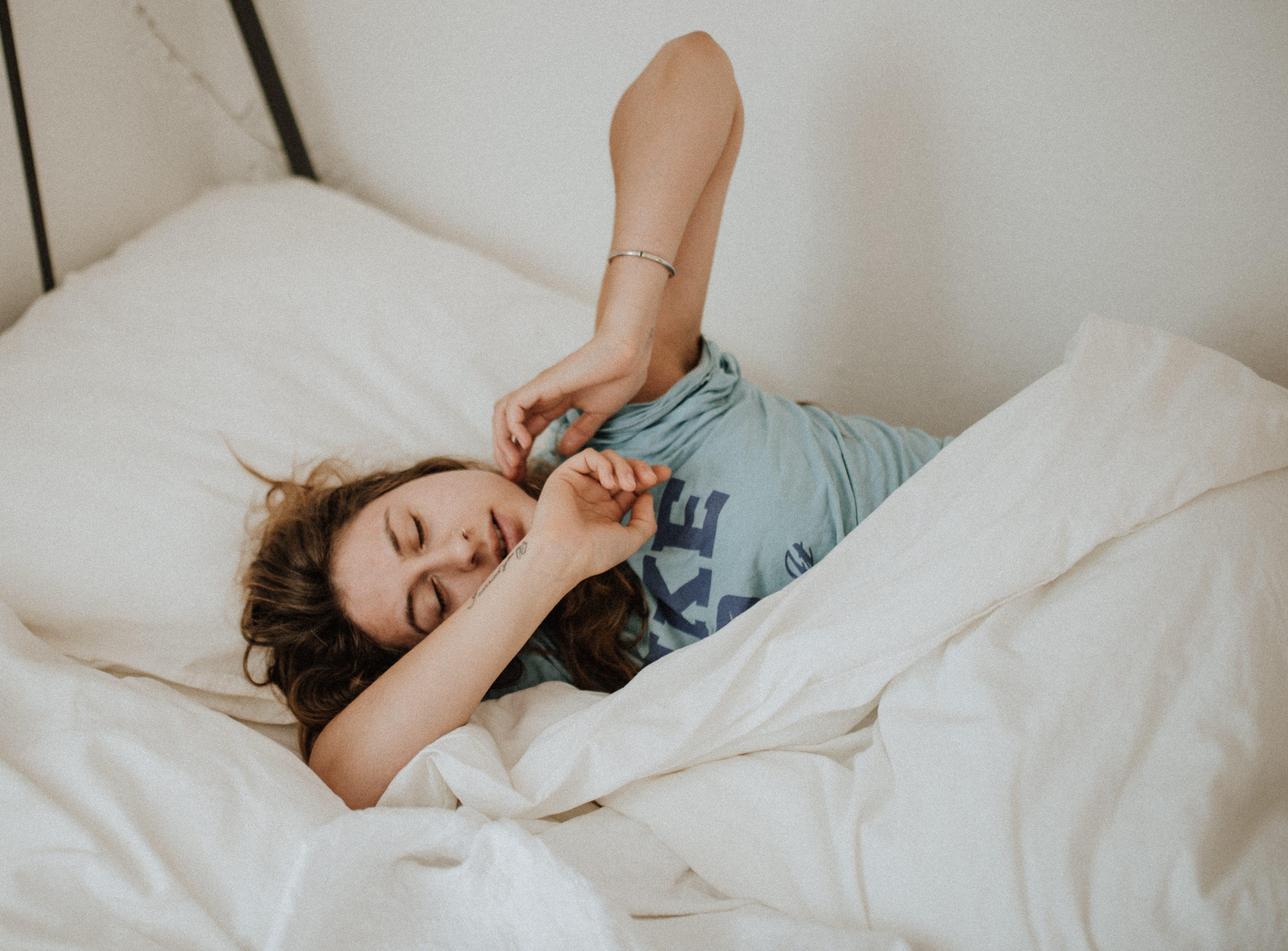 En tjej som ligger i en säng med vita lakan. Hon har brunt hår och en ljusblå T-shirt på sig.