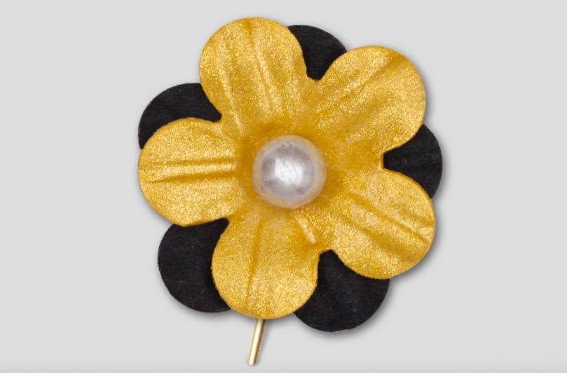 En pappersblomma på en nål. Blomman är guldig med svarta blad runt.