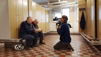 Ett omklädningsrum. På en bänk framför en rad med skåp sitter två äldre män. De har blå overaller på sig och tittar på ett foto. Framför dem sitter Nils Petter Löfstedt på knä och filmar dem med sin kamera.