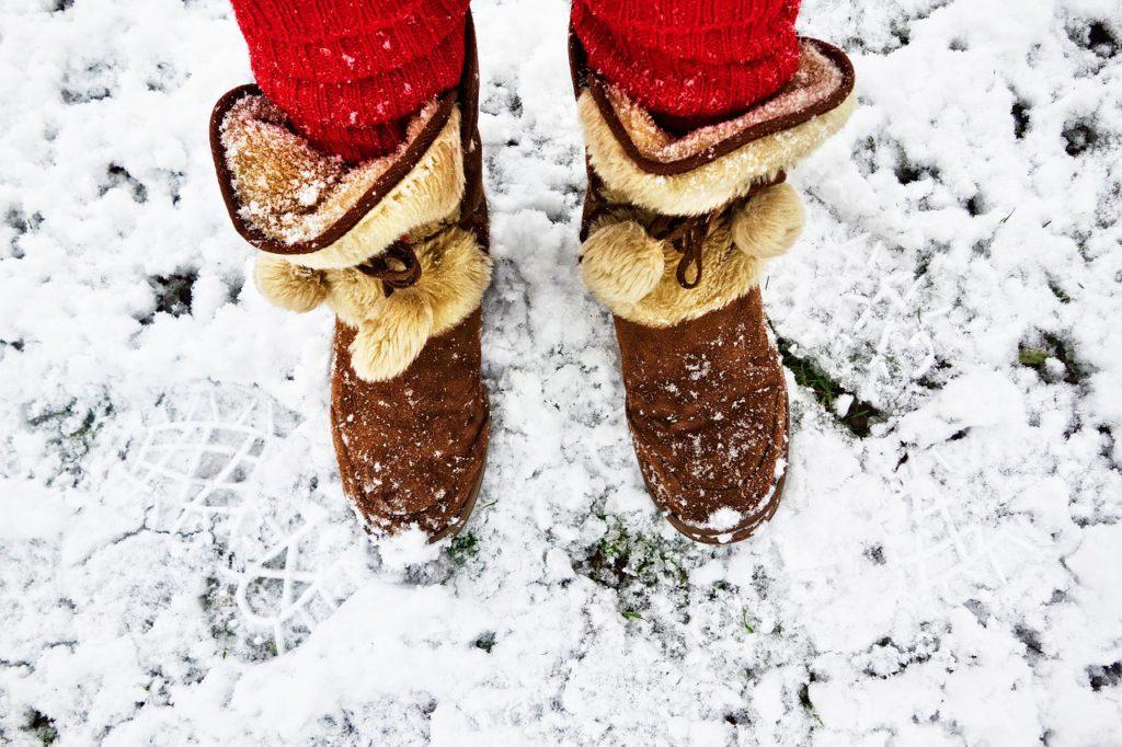 En person med bruna fluffiga vinterskor står i snö