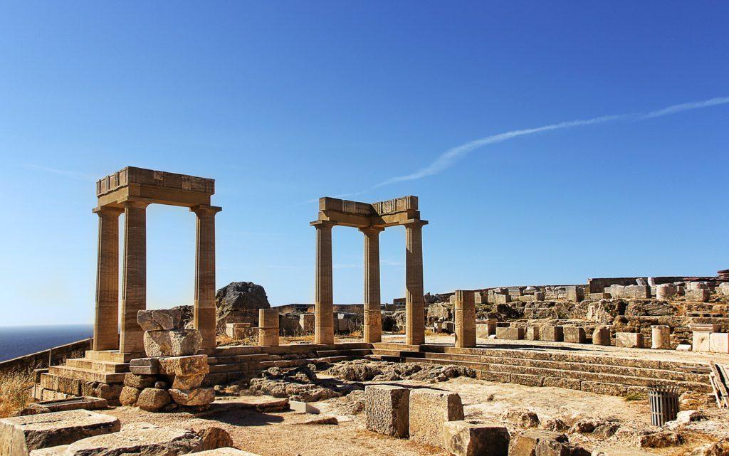Några stenpelare reser sig upp mot en blå himmeln mellan andra ruiner.