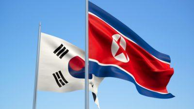 Två flaggor på varsin flaggstång. Till vänster är en vit flagga med en röd och blå cirkel. Till höger är en röd flagga med en blå rand längst upp och längst ner. I mitten av det röda syns en röd stjärna omgiven av en vit cirkel.
