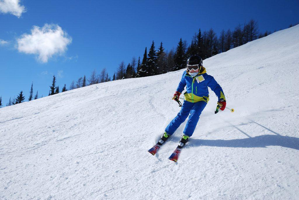 En person i blå och gula kläder åker skidor nerför en solig, snöig backe.