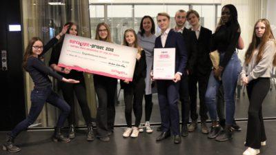 Delar av klass 8F står uppradade framför kameran. Några av eleverna håller i en stor check på 25000 kronor. En annan elev håller i ett diplom.
