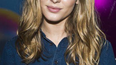 Zara Larsson tittar in i kameran. Hon har långt blont hår och en blå skjorta.