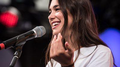 Dua Lipa står på en scen framför en mikrofon. Hon har långt brunt hår och en vit t-shirt. Hon ler stort.