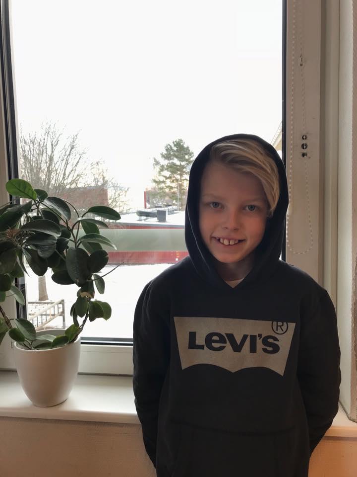Elias står framför ett fönster. Ute är det snö. Elias har en svart hoodie med luvan uppe. Han har blond lugg som ligger åt sidan.