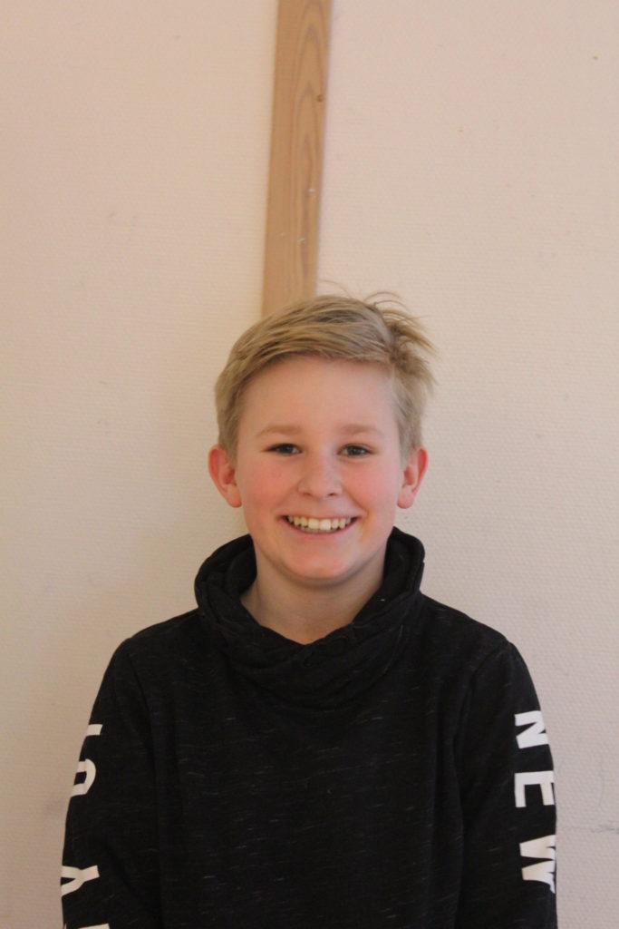 Gustav står framför en vit vägg. Han har svart tröja och blont rufsigt hår. Han ler stort.
