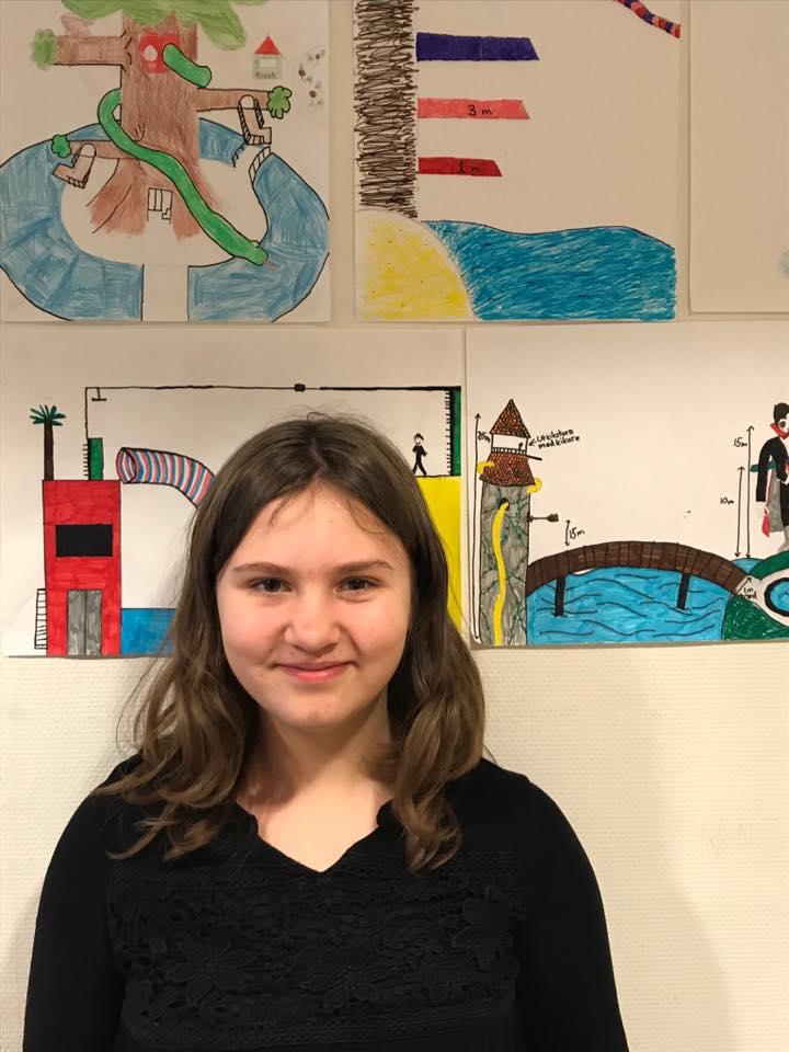 Madeleine står framför en vägg med teckningar. Madeleine har vågigt brunt hår och ler mot kameran.