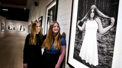 Två personer framför ett foto i ett galleri. I galleriet hänger fotografier. Ett fotografi är på en av personerna som står i galleriet. Personen på fotografiet har en ljus klänning. Personen håller i sitt hår.