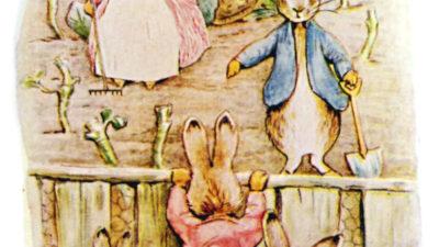 Tre kaniner i kläder står i ett trädgårdsland