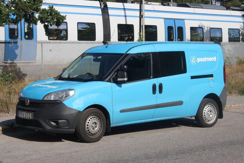 En ljusblå Postnord bil