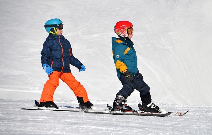 Två barn står på slalomskidor. De har färgglada täckkläder, hjälmar och skidglasögon.