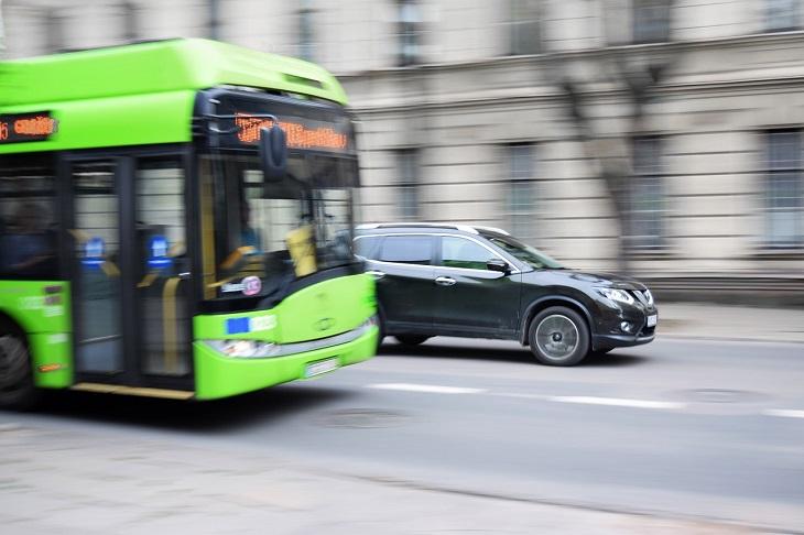 En grön buss åker på en väg. Bredvid den åker en svart bil. Bilden är lite suddig som om den har tagits i farten.