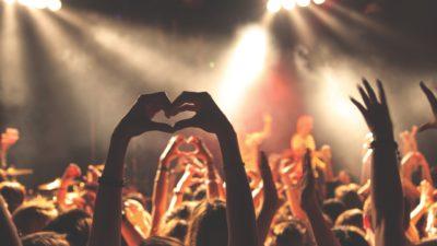 Människor på en konsert sträcker upp sina händer och formar ett hjärta