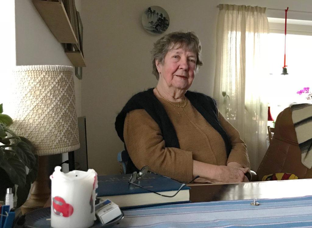 Dorothy Samuelsson har en svart väst över en brun tröja. Hon sitter vid ett bord i sitt vardagsrum.