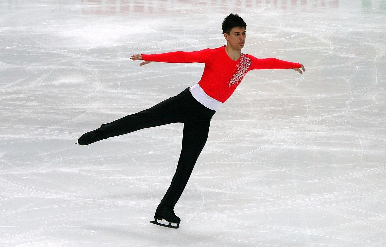 En manlig konståkare. Han har på sig en röd tröja och svarta byxor.