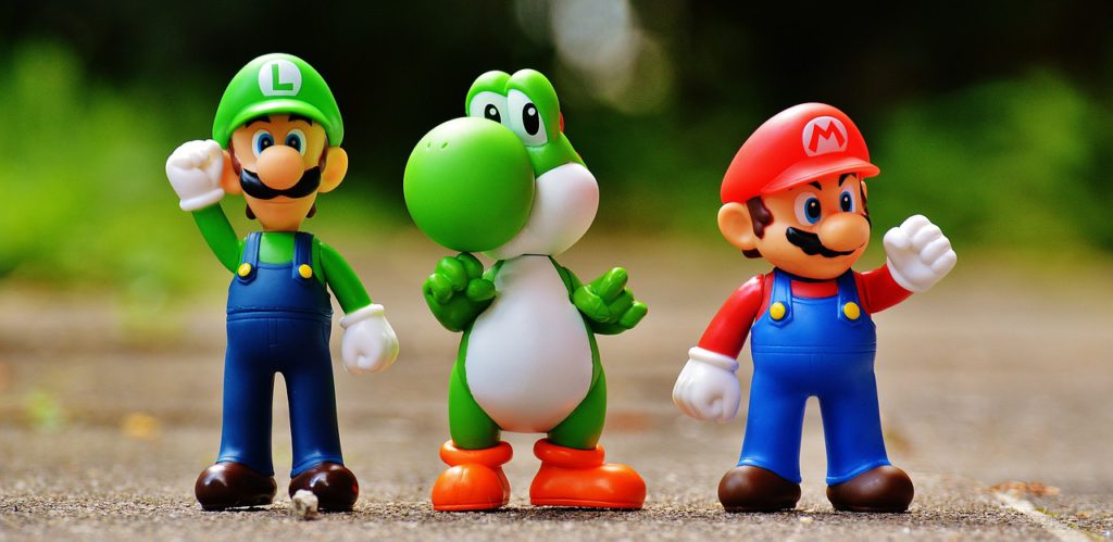 Tre leksakerfigurer som föreställer Luigi, Yoshi och Mario.