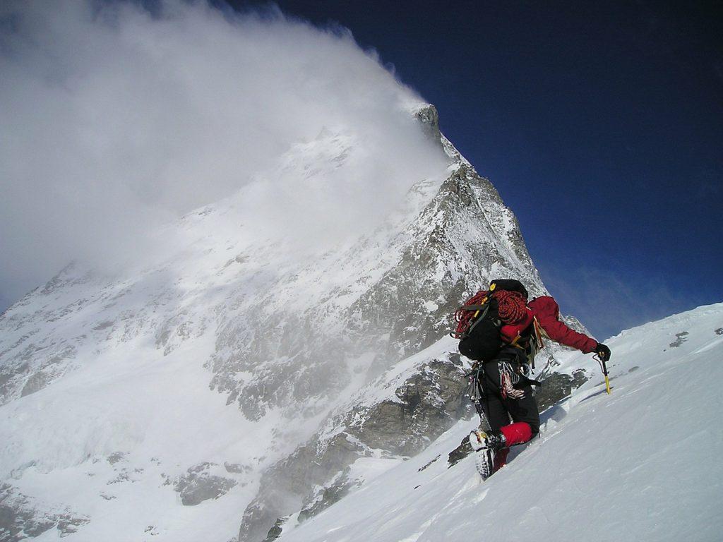 Ett stort berg sträcker sig mot himlen. I förgrunden syns en person som klättrar uppför en snöig bergvägg. Personen har röda och svarta täckkläder och en stor ryggsäck med rep hängandes utanpå. Personen har en vass pinne som hen har stuckit i snön för att kunna dra sig upp.
