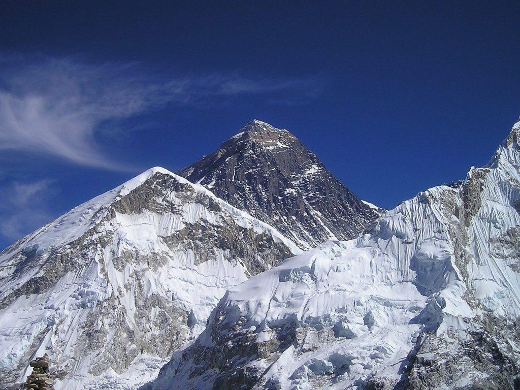 Mount Everest topp sticker upp bakom ett annat berg. Toppen är svart med lite snö på. Himlen är klarblå.
