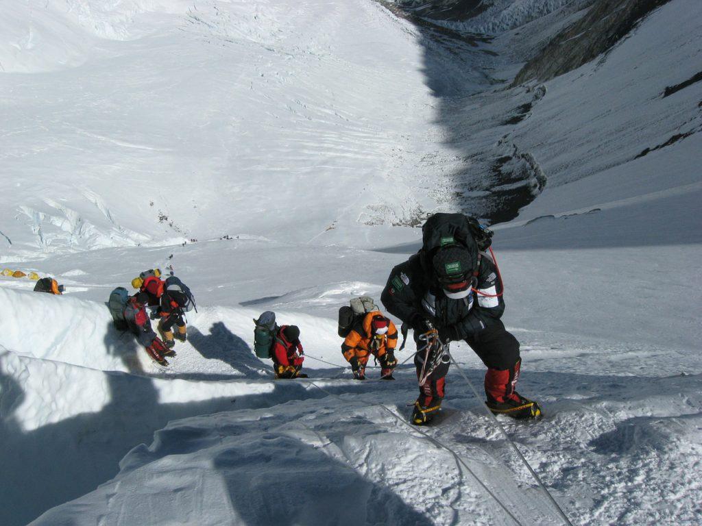 Bilden är tagen uppifrån. Nedanför syns flera personer som klättrar upp för en snöig bergssida. Människorna är fast knutna i ett snöre som de hänger i, samtidigt som de har fötterna mot bergsväggen. Alla har väldigt varma täckkläder, skidglasögon och stora mössor.
