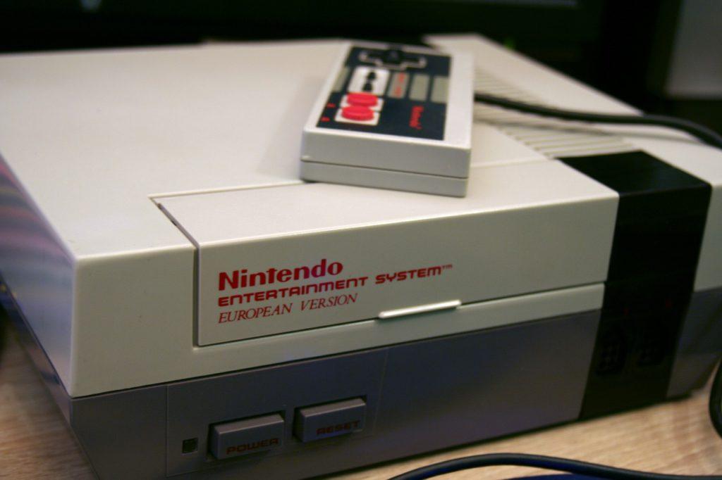 En grå plastbox som det står Nintendo på. Ovan på boxen ligger en spelkonsol.
