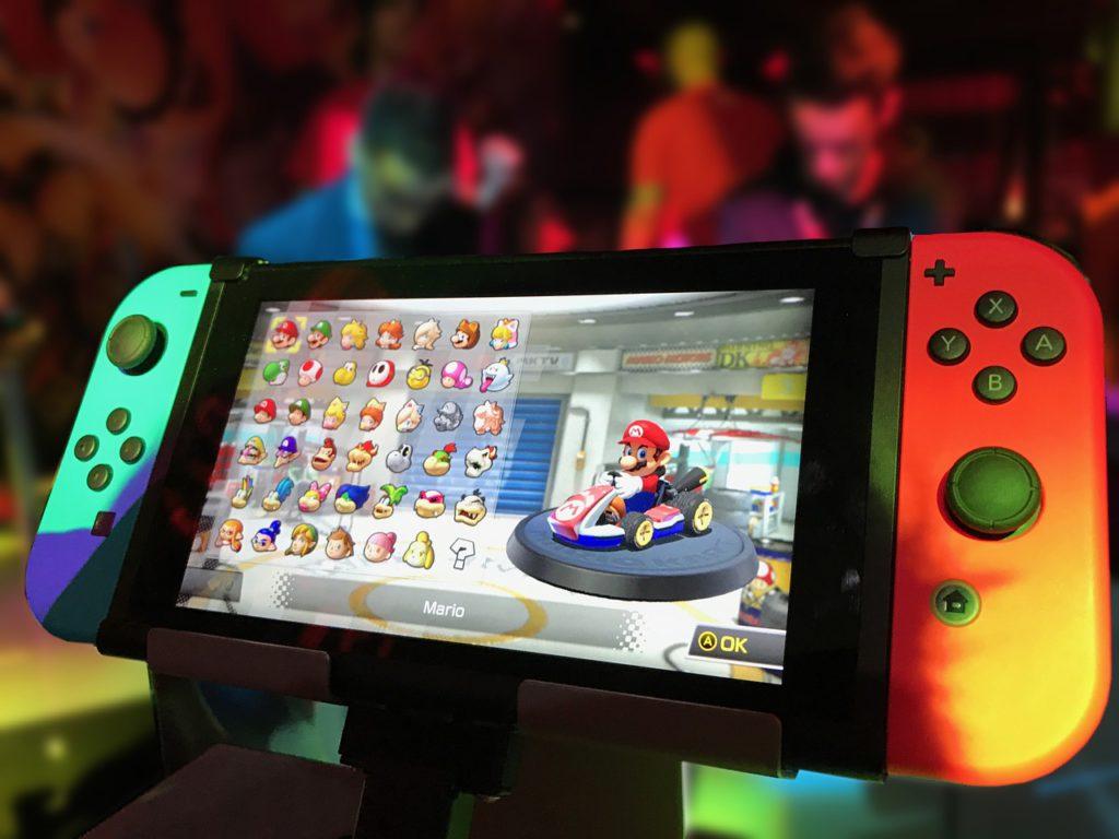 Ett Mario-spel syns på en skärm. Mario sitter i en liten racerbil.