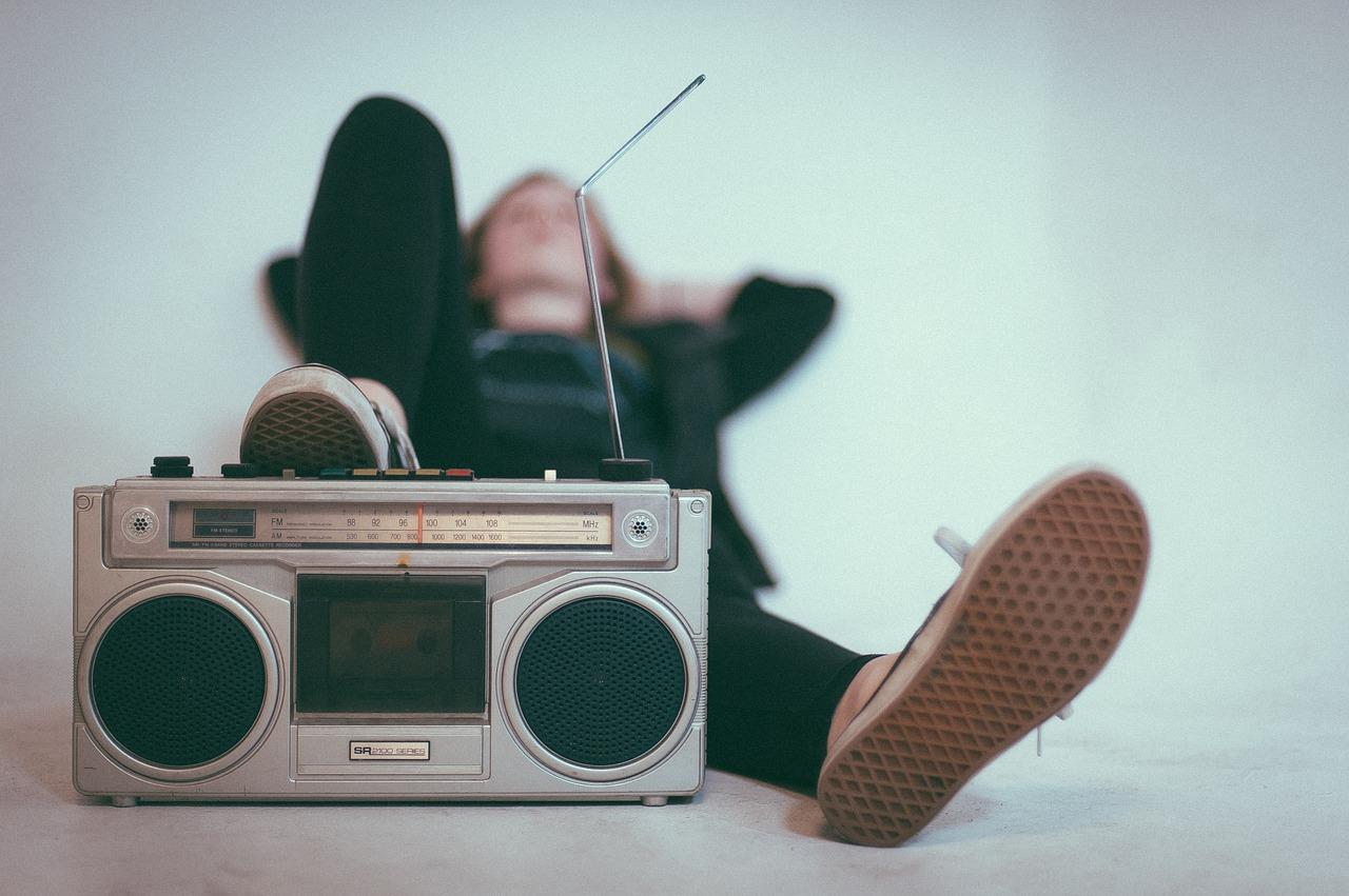 En grå radio med kassettbandspelare. I bakgrunden syns en tjej med svarta kläder som lutar sig tillbaka.