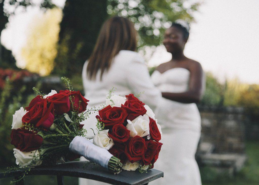 Två buketter med rosor ligger framför ett brudpar i vita kläder