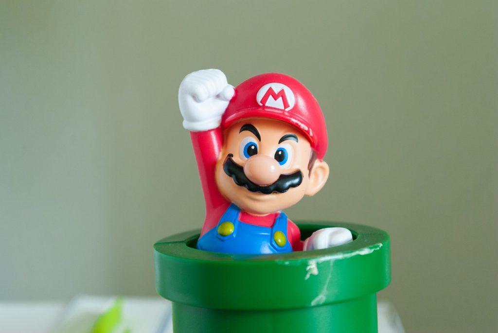 En Mario-figur sticker upp ur ett grönt rör.
