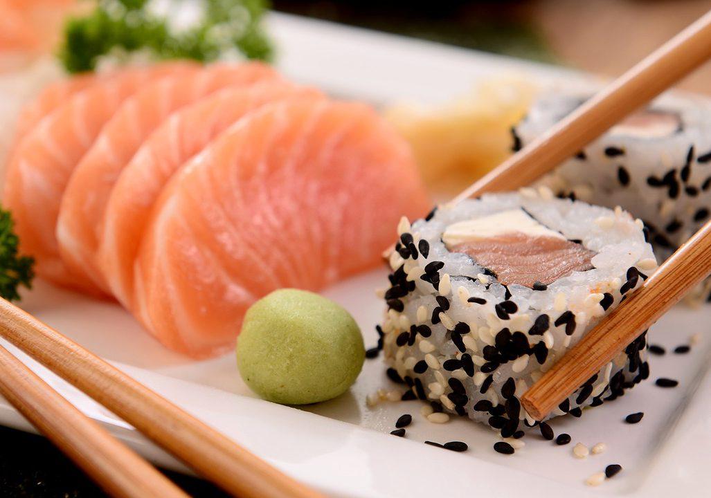 sushi och ätpinnar på en vit tallrik