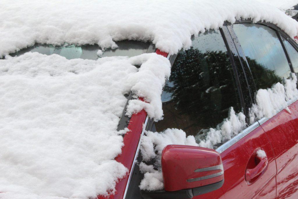 En snötäckt röd bil
