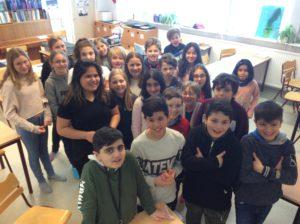 En gruppbild på barn som står i ett klassrum.