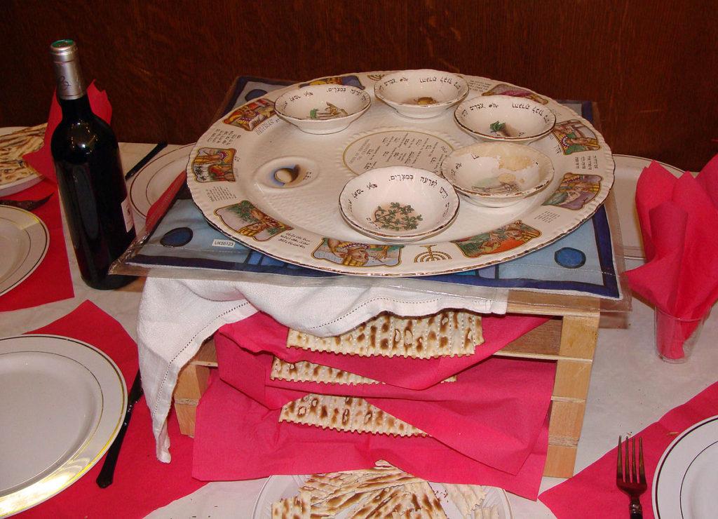 Ett bord med tallrikar. I mitten står en träställning med flera hyllor. På varje hylla ligger ett platt bröd. Överst står en tallrik med flera små skålar. Bredvid står en flaska med vin.