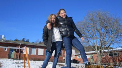 Två barn på en snöhög framför en skola. Himlen är blå. Barnen är glada.