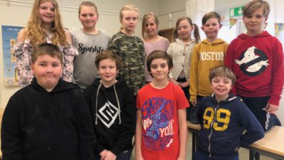 Klass 4D står i sitt klassrum. De är uppställda i två rader och tittar ni i kameran. De är 12 personer som alla har olika kläder.