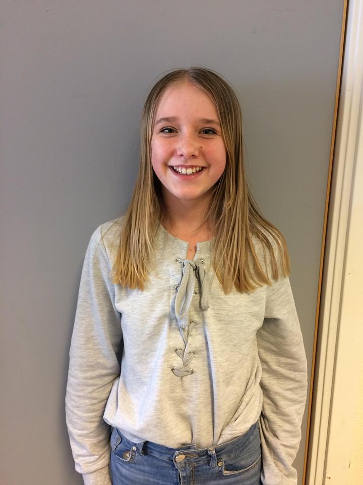 Agnes står framför en grå vägg och ler stort. Hon har långt blont hår och en grå tröja med snörning i fram.