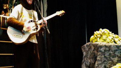 Klasse har på sig en apdräkt och står framför en mick med gitarr. På ett bord intill ligger mängder med bananer.