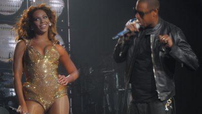 Beyoncé och Jay-Z uppträder på scen. Beyoncé har en glittrig baddräkt på sig och ler stort. Jay-Z har svarta kläder och sjunger i sin mikrofon.