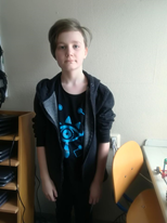 Emil står mellan en stol och en hylla. Han har svarta byxor, en svart t-shirt med blått tryck och en svart hoodie. Han har halvlångt rågblont hår som ligger åt ena sidan.