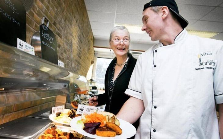 Två vuxna personer tittar på varandra och ler. De står framför en lunchservering. Den ena håller upp en tallrik med mat. Den andra lägger upp mat på sin tallrik.