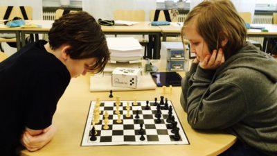 Två barn sitter mitt emot varandra i ett klassrum och tittar på ett schackbräde som ligger på bordet.