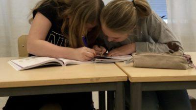 Två barn sitter bredvid varandra och skriver i en skolbok tillsammans.