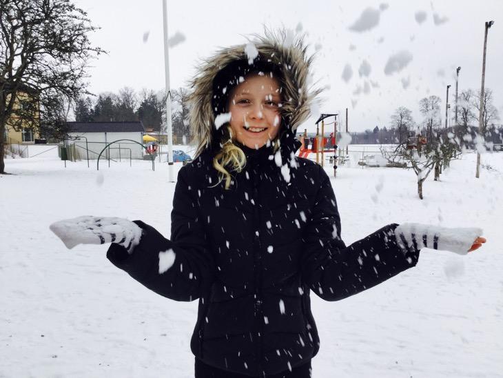 Vinterklätt barn står på snöig skolgård och kastar snö framför sig.