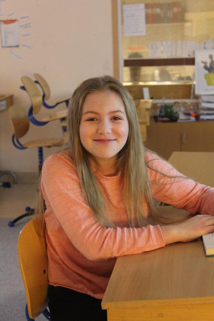 Agnes sitter vid en skolbänk och vrider sig åt sidan för att titta in i kameran. Hon har långt blont hår och en aprikosfärgad tröja.