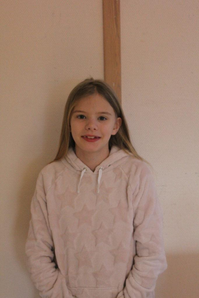 Saga står framför en vit vägg. Hon har en ljusrosa tröja med rosa stjärnor på och långt halvblont hår som hänger ner över hennes rygg.