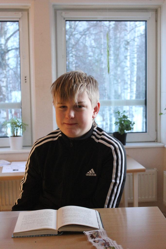 Oscar sitter bakom en skolbänk med ett fönster bakom sig. Han har kort blont hår med lugg som ligger ner i pannan, och en svarta adidaströja med vita ränder på armarna.