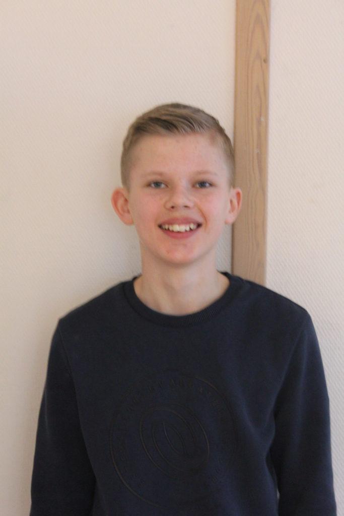 Adam står framför en vit vägg. Han har en blå längärmad tröja och blont hår med lugg som ligger åt sidan. Han ler mot kameran.