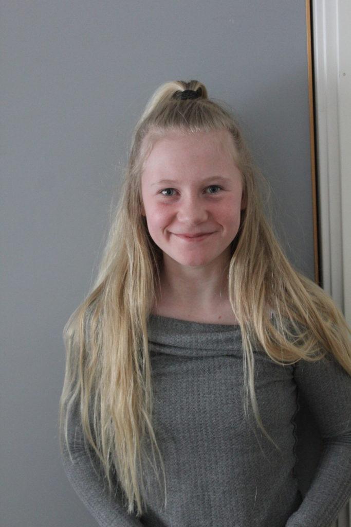 Emilia står framför en grå vägg. Hon har en grå tröja. Hon har långt blont hår där det främst håret är uppsatt i en tofs på huvudet.