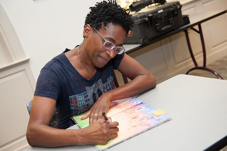 Jacqueline sitter vid ett bord. Hon skriver längst fram i en barnbok. Jacqueline har mörkt kort hår, glasögon och en mörkblå t-shirt.